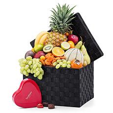 Découvrez ce panier élégant rempli à ras bord avec une sélection de fruits exotique et une jolie boîte-cadeau avec des pralines de Neuhaus.