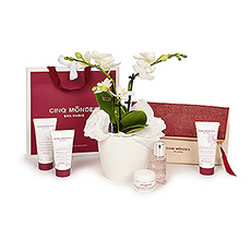 A charming gift bag with Cinq Mondes luxury French beauty products is presented with a luxurious mini orchid in this elegant gift set.