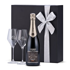 A sophisticated bottle of Champagne Lenoble Premier Cru Blanc de Noirs is presented in a luxury black gift box with a pair of signature glasses.