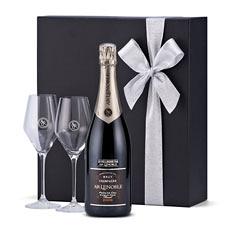Une magnifique bouteille de Champagne Lenoble Premier Cru Blanc de Noirs présentée dans un luxueux coffret noir avec deux verres à l'effigie de la marque.
