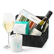 Un joli panier cadeau garni de produits de bien-être de la marque luxueuse Cinq Mondes et dune bouteille de vin blanc.