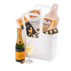 "A handy reusable Koziol ""Taschelino"" white tote is filled with a delicious collection of Dutch cheese, gourmet crisps, Belgian chocolates, and Champagne for a picnic on the go."