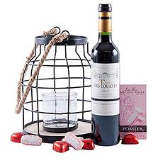 Ravivez la flamme de votre relation grâce à une bouteille de vin rouge (50 cl), des chocolats en forme de cœur et des biscuits roses doux près de chandelles romantiques.