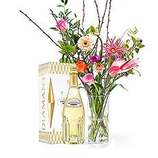 Une bouteille de champagne Pommery est accompagnée d'un beau bouquet de fleurs tropicales et colorées dans un vase intemporel.
