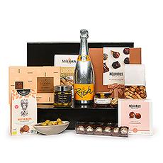 """Nous vous présentons l'un de nos cadeaux les plus exquis :l'Ultimate Gourmet avec le formidable champagne Veuve Clicquot """"Rich"""", le premier champagne créé spécialement pour être associé aux glaçons et à un ingrédient frais. Le superbe champagne est accompagné d'une sélection soigneusement sélectionnée des meilleures spécialités gastronomiques européennes et de chocolats belges de luxe."""