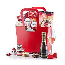 Un mousseux espagnol, des chocolats à croquer, des biscuits savoureux et d'autres délices sont présentés dans un sac Koziol rouge.