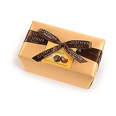 Le ballotin Belge classique et élégant est enveloppé dun luxueux papier doré rehaussé dun ruban noué à la main et garni dun somptueux assortiment de chocolats de qualité Godiva.