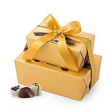 Deux ballotins dorés de Godiva sont liées avec un luxueux ruban doré et présentées dans un élégant cabas doré.