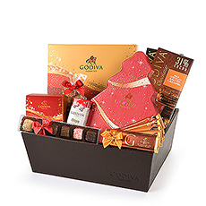 Delight everyone on your Christmas list this year with this luxury Christmas gift basket by Godiva. New for Christmas 2020, discover chocolates that literally sparkle with joy: the Godiva Sparkles Christmas Collection, featuring five unique holiday chocolates dusted with edible glitter. Paired with a festive Christmas Tree Gift Box, charming holiday chocolate figures, and a bounty of chocolate bars, tablets, mini Pearls, and truffles, this Godiva gift basket is the most delicious way to say Merry Christmas to your family and friends this year.